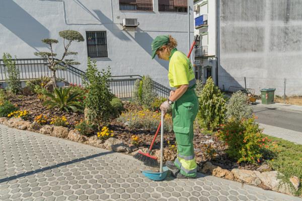 operaria barriendo jardin